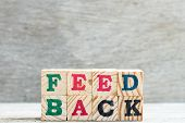 Letter Block In Word Feedback On Wood Background poster