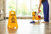 Safety Sign With Phrase Caution Wet Floor And Cleaner Indoors. Cleaning Service poster