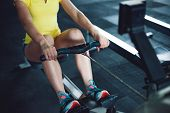 Rowing In The Gym. Young Woman Training Using A Rowing Machine poster