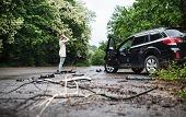 Young Woman Standing By The Damaged Car After A Car Accident. poster