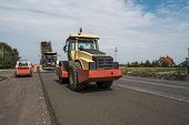 Yellow Red Heavy Vibration Roller Compactor At Asphalt Pavement Works For Road Repairing. Working On poster