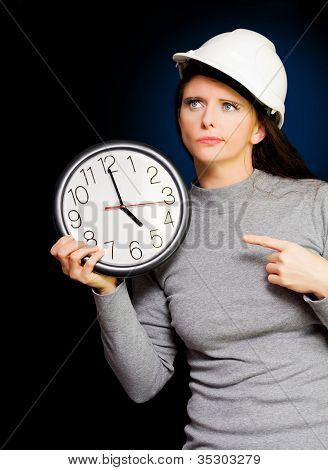 Female Construction Builder Pointing At Clock