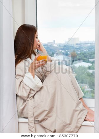 Woman drinking an orange juice.