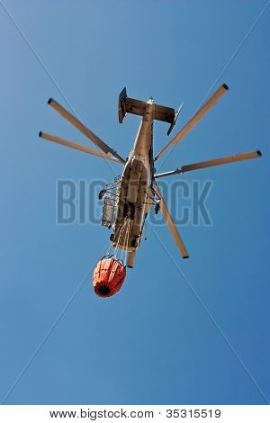 helicopter firefighter with water in Spain forest fire