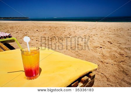Glass Of Juice Next To Beach.