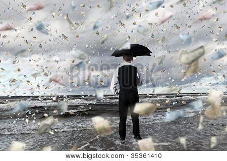 Business person under money rain