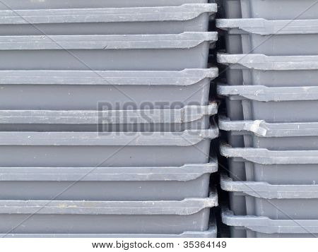 Stack of empty grey plastic fishery containers