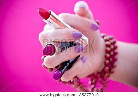 Hand Holding Lipsticks With Purple Nailpolish & Bracelets