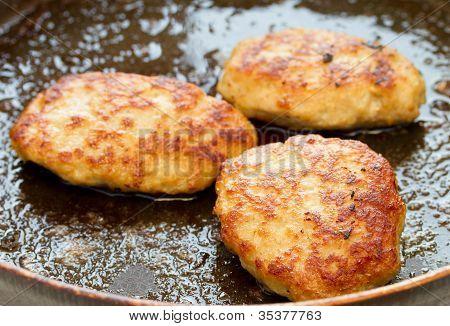 Meatballs frying in a pan