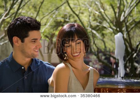Closeup Of Young Couple With Man Gazing At Woman With Fountain In Background