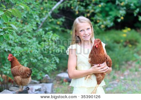 Young Blonde Girl In The Garden With Her Chickens