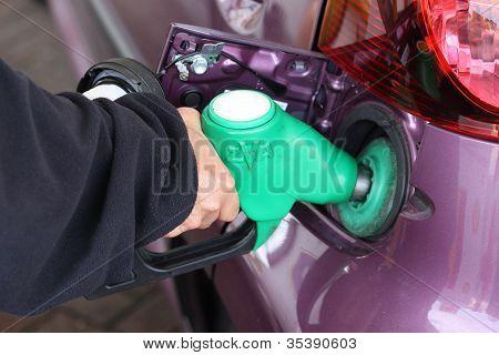 Llenado de un tanque de gasolina del coche de la mujer