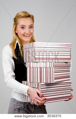 Smiling Young Woman With Stack Of Boxes