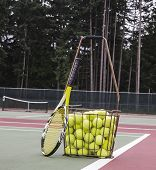 foto of hopper  - Tennis balls hopper and racket on court with trees and sky in background - JPG