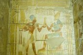 foto of horus  - Ancient Egyptian bas relief showing the Pharaoh Seti I taking the royal flail from the god Horus with goddess Maat standing behind him.  Inner chapel at Abydos Temple, el Balyana, Egypt.