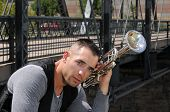 stock photo of trestle bridge  - A trumpet player in the city by an old trestle bridge - JPG