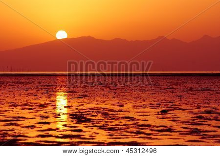 Sun Is Setting Down Above Sea Waters And Hills