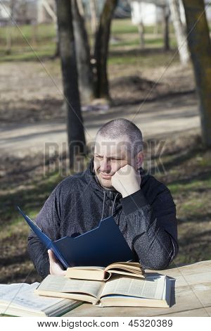 Tired man reading a book outdoors on a bench