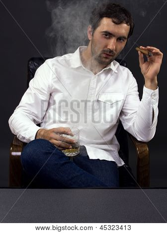 Man Smoking A Cigar With A Glass Of Whiskey