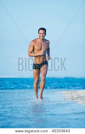 Man running in water on the beach