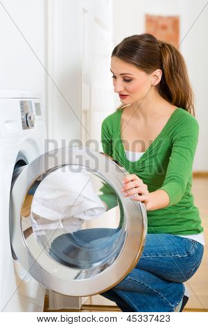 Young woman or housekeeper has laundry day at home, she takes the out of the washing machine or the dryer