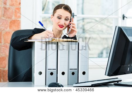 Young businesswoman working in her Office, she sits behind folders and on the telephone is a customer or client