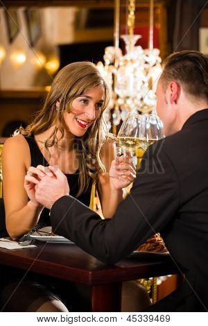glückliches Paar-haben-ein romantisches Date in einem feinen Brille Speiserestaurant, sie trinken Wein und Klirren,