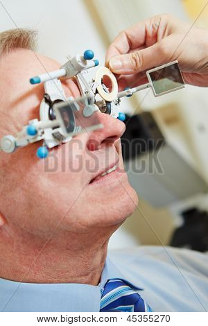 Elderly man with trial frame and trial glasses at optician