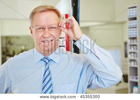 Smiling elderly man with new glasses at the optician