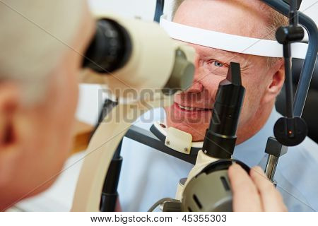 Senior man at optician looking in slit lamp to get his cornea examined
