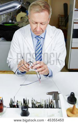 Optician in workshop fixing glasses with pliers