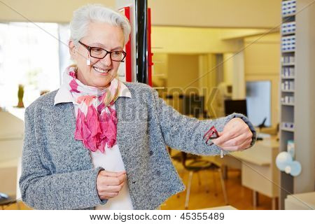 Elderly smiling woman comparing glasses at the optician