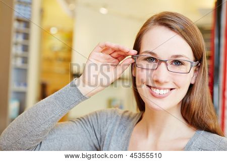 Attractive woman with new glasses in optician retail store