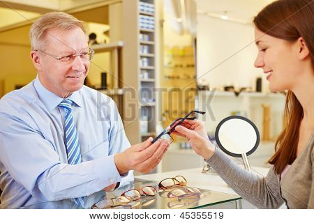 Senior optician selling new glasses to a young female customer