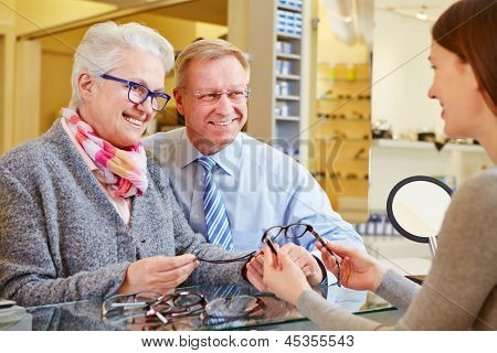 Optician consulting senior couple for buying new glasses