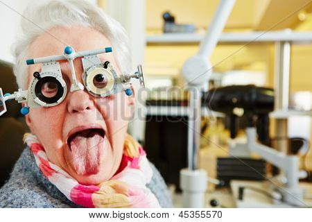 Elderly woman with a trial frame sticking out tongue at the optician