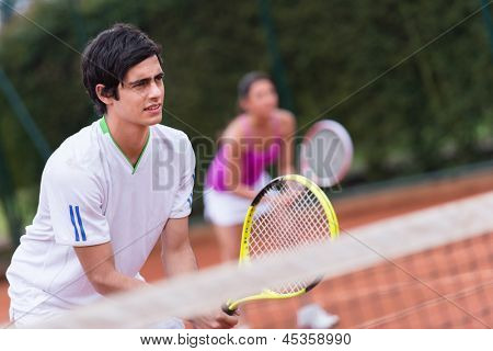 Tennis players at the court playing a doubles match