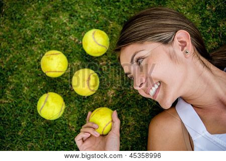 Female tennis player lying on the lawn with balls