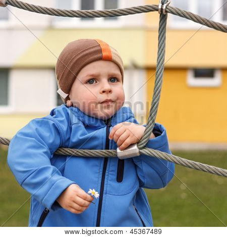 Young Boy Holding Flower On The Playground