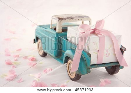 Antique Toy Truck Carrying A Gift Box With Pink Ribbon
