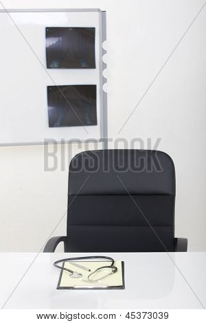 Doctor Office Table Desk And Black Chair With Stethoscope  And White Paper