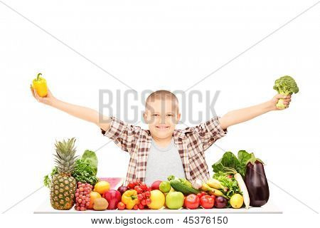 An excited kid holding broccoli, and a pepper on a table full of fruits and vegetables, isolated on white background