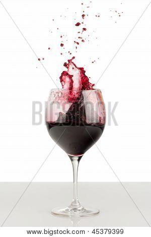 Splash Of Red Wine In A Wineglass.
