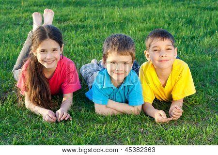 Three happy kids lying on the field