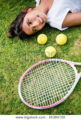 Portrait of a female tennis player lying on the lawn