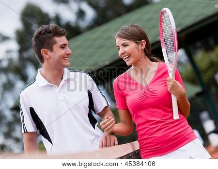 Couple of players at the tennis court looking happy