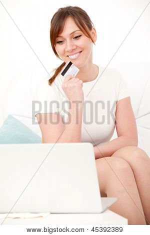 Portrait of young woman sitting on sofa using laptop with card in her hand and giving you an attractive smile