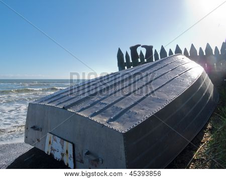 Aluminum fishing boat and boots drying on fence