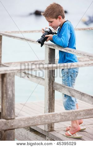 Portrait of little boy photographing outdoors