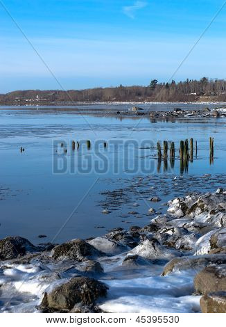 Icy Shore And Distant Pilings